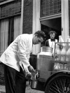 Een melkboer aan huis tapt melk in een melkkannetje vanuit een grote melkkan die achterop zijn kar staat. op de achtergrond kijkt de klant toe, vermoedelijk een huishoudster. Plaats onbekend, 1956.